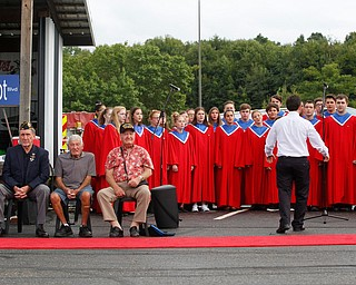 The Austintown Fitch High School concert choir sings while, from left, Joe Brown, a U.S. Army veteran of Vietnam, Charles Jaros, a U.S. Army veteran of Vietnam, James Kenneally, a U.S.M.C veteran of Korea, and Roy Gallatin, a U.S.M.C veteran of World War ||, four of the 13 veterans honored at the Austintown Patriot Day ceremony, listen in front of them outside of Quaker Steak and Lube in Austintown on Thursday. EMILY MATTHEWS | THE VINDICATOR