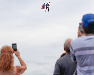 People watch and take photos as Jimmy Drummond, of Youngstown, skydives at the Austintown Patriot Day ceremony outside of Quaker Steak and Lube in Austintown on Thursday. EMILY MATTHEWS | THE VINDICATOR