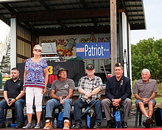 Kathy Tuomala, a U.S Army veteran of Iraq, Afghanistan, Desert Storm, and Iraqi Freedom, stands as she is honored with 12 other veterans at the Austintown Patriot Day ceremony outside of Quaker Steak and Lube in Austintown on Thursday. EMILY MATTHEWS | THE VINDICATOR