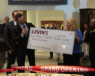 Neighbors | Jessica Harker.Chris Pelcher awarded a check for $2,500 to the Akron Childrens Hospital's Beeghly Campus during the ribbon cutting opening ceremony August 31.