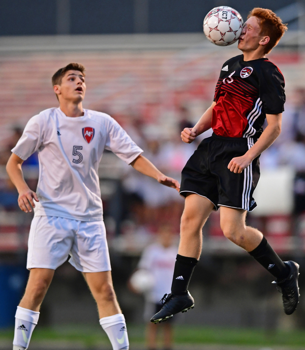 CANFIELD, OHIO - SEPTEMBER 6, 2018: Canfield's Jake Johnson heads the ball away from Fitch's Dom Foley during the first half of their game, Thursday night at Canfield High School. DAVID DERMER | THE VINDICATOR