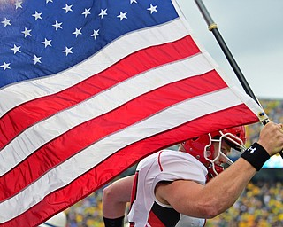 MORGANTOWN, WEST VIRGINIA - SEPTEMBER 8, 2018: Youngstown State's Montgomery VanGorder runs onto the field with the American flag before the start of Saturday nights game against West Virginia. DAVID DERMER | THE VINDICATOR