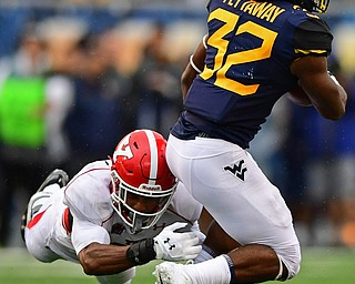 MORGANTOWN, WEST VIRGINIA - SEPTEMBER 8, 2018: West Virginia's Martell Pettaway is tackled by Youngstown State's Avery Larkin during the first half of their game, Saturday night. DAVID DERMER | THE VINDICATOR