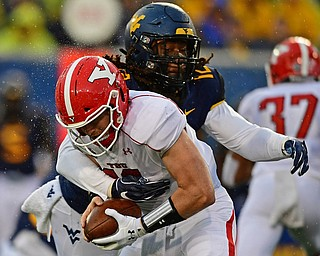 MORGANTOWN, WEST VIRGINIA - SEPTEMBER 8, 2018: Youngstown State's Montgomery VanGorder is tackled for a loss by West Virginia's Jabrill Robinson during the first half of their game, Saturday night. DAVID DERMER | THE VINDICATOR