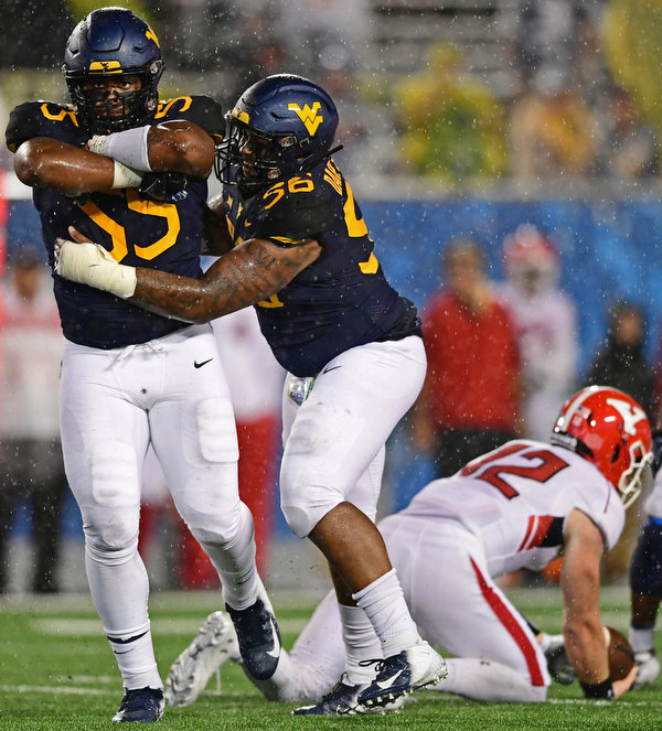 MORGANTOWN, WEST VIRGINIA - SEPTEMBER 8, 2018: West Virginia's Dante Stills celebrates while being congratulated by Darius Stills after sacking Youngstown State's Montgomery VanGorder during the second half of their game, Saturday night. West Virginia won 52-17. DAVID DERMER | THE VINDICATOR