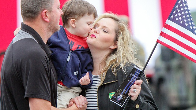 Columbiana residents Jason Stokes, his wife Melissa and their son Aidan, 3, share a moment during Austintown's service Tuesday at the 9/11 Memorial Park along South Raccoon Road. The Stokes learned of the Sept. 11, 2001, attacks while working together at a service plaza along the Ohio Turnpike.