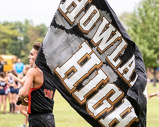 DIANNA OATRIDGE | THE VINDICATOR Howland's Angelo Mauri waves his school banner during the  Suburban Cross Country meet at Austintown Park on Tuesday.