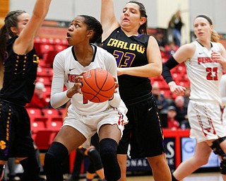 YSU's Amara Chikwe looks towards the hoop while Carlow's Emma Stille, left, and Bria Rathway, right, try to block her during their game Friday night at YSU. EMILY MATTHEWS | THE VINDICATOR