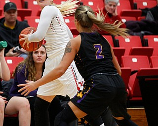 YSU's Alison Smolinski looks to pass the ball as Carlow's Delaney Daly tries to block her during their game Friday night at YSU. EMILY MATTHEWS | THE VINDICATOR