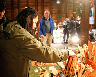Kathy Trinh, of Philadelphia, looks at wooden kitchen utensils carved by Gregg Kristophel, of Harmony, Pa., right, with her boyfriend Cory Ryhal, of Boardman, left, at Lanterman's Mill Olde Fashioned Christmas on Saturday. EMILY MATTHEWS | THE VINDICATOR
