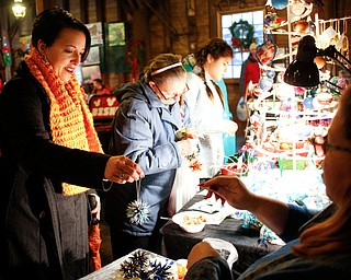 Robin Blose, of Kittanning, Pa., buys a Christmas ornament from Shawne Wilfong, of Austintown, at Lanterman's Mill Olde Fashioned Christmas on Saturday. EMILY MATTHEWS | THE VINDICATOR