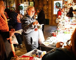 Robin Blose, of Kittanning, Pa., left, and her aunt Barb Soloski, of Youngstown, look at and buy Christmas ornaments from Lindy Young and Shawne Wilfong, both of Austintown, at Lanterman's Mill Olde Fashioned Christmas on Saturday. EMILY MATTHEWS | THE VINDICATOR