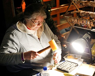 Kathy Bowman, of Austintown, personalizes and sells leather bracelets at Lanterman's Mill Olde Fashioned Christmas on Saturday. EMILY MATTHEWS | THE VINDICATOR