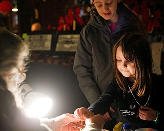 Samantha Edwards, 6, of Canfield, gets a personalized leather bracelet with her name on it from Kathy Bowman, of Austintown, while Edwards' sister, Sophia Edwards, 10, stands behind her at Lanterman's Mill Olde Fashioned Christmas on Saturday. EMILY MATTHEWS | THE VINDICATOR