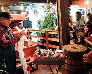 Joe Sullivan, of Boardman, makes balloon sculptures for kids at Lanterman's Mill Olde Fashioned Christmas on Saturday. EMILY MATTHEWS | THE VINDICATOR