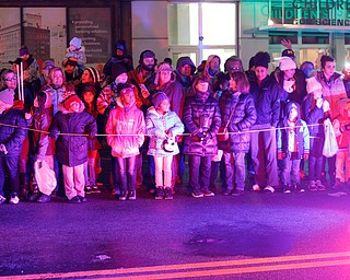 People watch as Youngstown Police officers drive by at the beginning of Youngstown's annual Holiday Parade on Friday night. EMILY MATTHEWS | THE VINDICATOR
