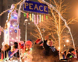 Kids from the Montessori School of the Mahoning Valley wave and throw out candy from the school's float in Youngstown's annual Holiday Parade on Friday night. EMILY MATTHEWS | THE VINDICATOR