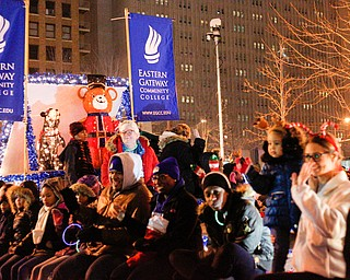 People sitting on Eastern Gateway Community College's float smile and wave to the crowd during Youngstown's annual Holiday Parade on Friday night. EMILY MATTHEWS | THE VINDICATOR