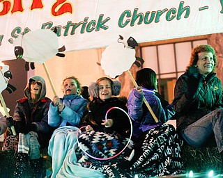 People ride on the back of the St. Patrick Parish float in Youngstown's annual Holiday Parade on Friday night. EMILY MATTHEWS | THE VINDICATOR