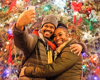 Robert Moore, of Youngstown, takes a selfie with Marquita Hall, of Youngstown, in front of the Christmas tree after the holiday parade and tree-lighting ceremony Friday night. EMILY MATTHEWS | THE VINDICATOR