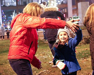 Cassi Samios, 7, of Brookfield, dances with family friend Karen Chaszeyka, of New Springfield, after the holiday parade and tree-lighting ceremony Friday night. EMILY MATTHEWS | THE VINDICATOR