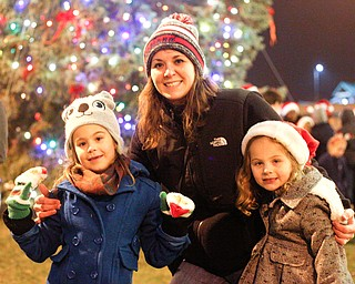 From left, Cassi Samios, 7, mom Lauren Samios, and Korie Samios, 5, all of Brookfield, pose in front of the Christmas tree after the holiday parade and tree-lighting ceremony Friday night. EMILY MATTHEWS | THE VINDICATOR