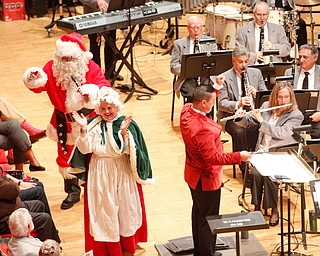 Santa greets the crowd with Mrs. Claus while The Packard Band plays Here Comes Santa Claus during The Packard Band annual Christmas Spectacular at W.D. Packard Music Hall on Sunday afternoon. EMILY MATTHEWS | THE VINDICATOR