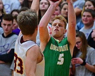 CANFIELD, OHIO - DECEMBER 4, 2018: Ursuline's Dylan Karlovic shoots a three point shot over South Range's Ben Irons during the first half of their game, Tuesday night at South Range High School. DAVID DERMER | THE VINDICATOR
