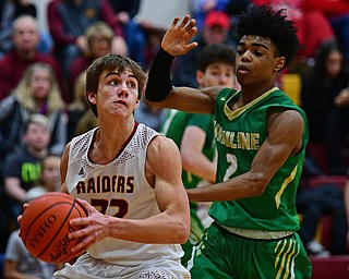 CANFIELD, OHIO - DECEMBER 4, 2018: South Range's Nick Matos drives on Ursuline's Daysean Harris during the first half of their game, Tuesday night at South Range High School. DAVID DERMER | THE VINDICATOR