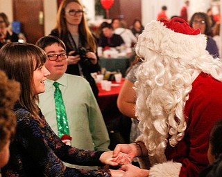 Katelyn Hall, 16, a student at Fitch High School, dances with Santa at the 18th annual Winterfest dance at The Mahoning Country Club on Wednesday night. EMILY MATTHEWS | THE VINDICATOR