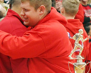 William D. Lewis The Vindicator   Girard AD Nick Cochran, left, hugs senior Jack Delgarbino during a 12-6-18 event at Girtard HS honoring the 2018 stste runners up football team.