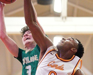 Ursuline's Pat McLaughlin catches a rebound as Cardinal Mooney's Terrell Brown reaches for it during their game at Cardinal Mooney on Friday night. EMILY MATTHEWS | THE VINDICATOR