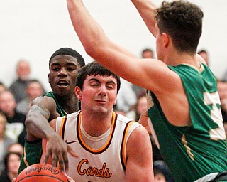 Ursuline's RJ Clark reaches from behind Cardinal Mooney's Pete Haas to hit the ball out of his hands while Ursuline's Luke Pipala tries to block in front of Haas during their game at Cardinal Mooney on Friday night. EMILY MATTHEWS | THE VINDICATOR