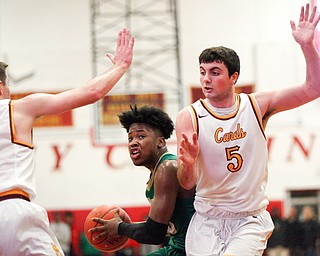 Ursuline's Travis Easterly looks to pass the ball as Cardinal Mooney's Pete Haas, right, and Anthony Fire try to block him during their game at Cardinal Mooney on Friday night. EMILY MATTHEWS | THE VINDICATOR