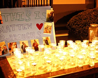 A poster a candles for Matthew Burroughs are displayed at a vigil for him outside of his Royal Mall Apartment on Saturday night. EMILY MATTHEWS | THE VINDICATOR