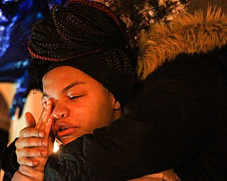 Ashantee Allen, 15, of Warren, speaks about her relationship with Matthew Burroughs as well as how she will miss seeing how happy Burroughs made her mom, Tara Elkins, who is hugging her, at a vigil for Burroughs outside of his Royal Mall Apartment on Saturday night. EMILY MATTHEWS | THE VINDICATOR