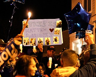 People hold up a poster for Matthew Burroughs as well as candles and balloons before releasing the balloons at the end of a vigil for Burroughs outside of his Royal Mall Apartment on Saturday night. EMILY MATTHEWS | THE VINDICATOR