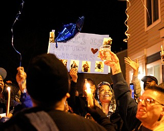 People hold up a poster and candles for Matthew Burroughs as balloons are released at the end of a vigil for Burroughs outside of his Royal Mall Apartment on Saturday night. EMILY MATTHEWS | THE VINDICATOR