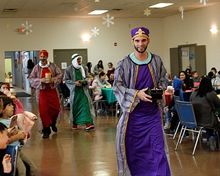 The Three Kings, Carlos Rosario, front, George Lopez, back left, and Jose Rene Vazquez, back right, all of Youngstown, walk in during Three Kings Day at OCCHA on Saturday afternoon. EMILY MATTHEWS | THE VINDICATOR