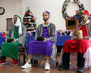The Three Kings from left, Jose Rene Vazquez, Carlos Rosario, and George Lopez, all of Youngstown, wait to hand out presents during Three Kings Day at OCCHA on Saturday afternoon. EMILY MATTHEWS | THE VINDICATOR