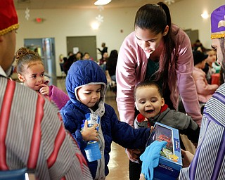From left, Janeliz Garcia, 4, Abel Garcia, 3, and Abriel Garcia, 2, receive presents from the Three Kings with their mother Lizabeth Garcia, of Youngstown, during Three Kings Day at OCCHA on Saturday afternoon. EMILY MATTHEWS | THE VINDICATOR