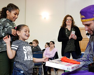Abrianalis Saldana, 11, right, and Joselyn Bonilla, 6, both of Youngstown, receive presents from one of the Three Kings, Carlos Rosario, of Youngstown, during Three Kings Day at OCCHA on Saturday afternoon. EMILY MATTHEWS | THE VINDICATOR