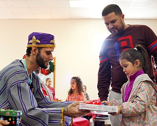 Ariadna Jimenez, 4, receives a present from one of the Three Kings, Carlos Rosario, of Youngstown, with her dad Francisco Jimenez, of Youngstown, next to her during Three Kings Day at OCCHA on Saturday afternoon. EMILY MATTHEWS | THE VINDICATOR