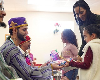 Sheylynn Muniz, 9, right, with her mom Sheila Santiago, and Daysha Ocasio, 9, all of Youngstown, receive gifts from the Three Kings, from left, Jose Rene Vazquez, Carlos Rosario, and George Lopez, all of Youngstown, during Three Kings Day at OCCHA on Saturday afternoon. EMILY MATTHEWS | THE VINDICATOR