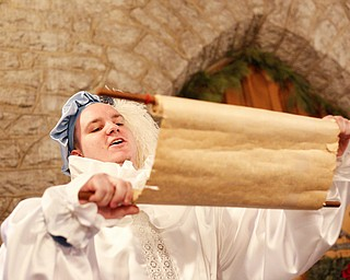 Anthony Humphrey, of Athens, Ohio, sings from a scroll before leading the Boar's Head Procession during the Boar's Head and Yule Log Festival at St. John's Episcopal Church on Sunday afternoon. EMILY MATTHEWS | THE VINDICATOR