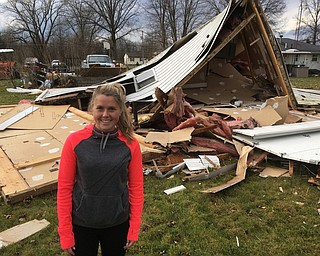 > Emily Metheny stands near the garage that was over a pickup truck on  her grandfather's property on North Park Avenue in Bazetta Township Tuesday. The truck is shown in the background. She watched the garage lift off of the ground, hang in the air and then fall to the ground Tuesday morning.