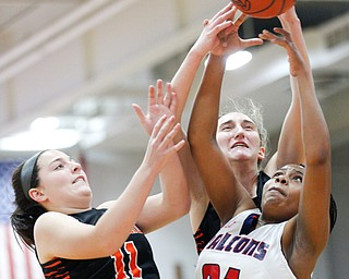 Fitch's Daria Williams, right, and Howland's Alyssa Pompelia, left, and Alex Ochman try to catch a rebound during the first half of their game at Fitch High School on Wednesday night. EMILY MATTHEWS | THE VINDICATOR