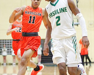 Ursuline's Daysean Harris and Massillon's Jaden Stock go after the ball during their game at Ursuline on Friday night. EMILY MATTHEWS | THE VINDICATOR