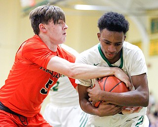 Ursuline's Jakylen Irving holds onto the ball while Massillon's  Anthony Pedro tries to grab it during their game at Ursuline on Friday night. EMILY MATTHEWS | THE VINDICATOR