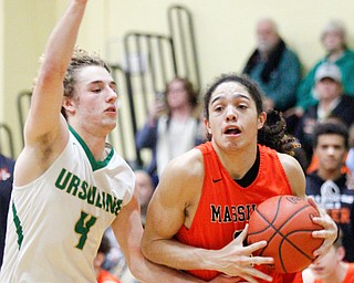 Massillon's Jayden Ballard drives the ball while Ursuline's Vince Armeni tries to block him during their game at Ursuline on Friday night. EMILY MATTHEWS | THE VINDICATOR